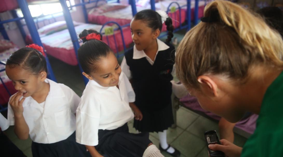 Projects Abroad vrijwilliger werkt met kinderen n Mexico helpt met het schoonmaken van de schoenen van kinderen in een Kinderopvang.